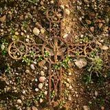 残破和生锈的在老生苔墓碑的铁土气耶稣受难象 宗教的被放弃的标志 图库摄影