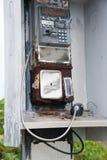 残破的公用电话手机和硬币回归 库存图片