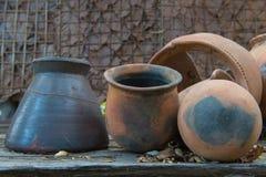 残破的古色古香的泥罐或传统瓶子在被放弃的小屋 免版税库存图片