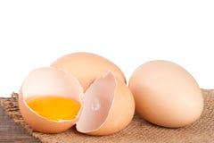 残破的在一张木桌上的鸡蛋用卵黄质和蛋壳有白色背景 库存照片