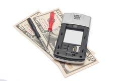 残破的在白色隔绝的手机和美元 库存图片