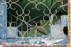 残破的大块玻璃在与酒吧的一个窗口里在一家被放弃的工厂厂房或工厂 免版税图库摄影