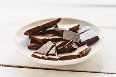 残破的巧克力在板材的在白色木桌上 库存图片