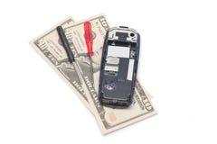 残破的手机和美元 免版税库存图片