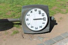 残破的手表拨号盘 有时钟的街道岗位在地面上说谎 免版税库存照片