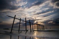 残破的木碰撞在海的桥梁和波浪在日落,攀牙,泰国期间 库存照片