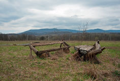 残破的树木繁茂的长凳和桌在草甸 图库摄影