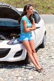残破的汽车最近的常设妇女 库存图片