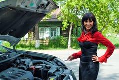 残破的汽车的年轻俏丽的微笑的妇女 免版税库存照片
