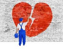 残破的爱的标志被绘在砖墙由人 库存图片