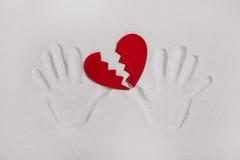 残破的红色心脏用手在爱憔悴的沙子打印 免版税库存照片