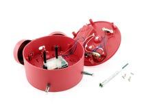 残破的红色闹钟机械设备有小在白色背景隔绝的金属螺丝刀和螺丝的 免版税库存图片
