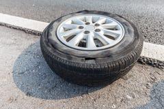 残破的轮胎损坏了投入在路边缘的表面上  免版税库存照片
