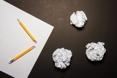 残破的铅笔,纸,弄皱了在黑背景的纸 免版税库存图片