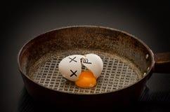 残破的鸡蛋用卵黄质在煎锅,被绘的面孔漏了 免版税库存照片