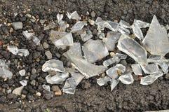 残破的玻璃修剪片断在沥青的 库存图片
