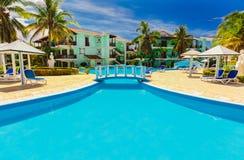殖民地旅馆地面、美丽的邀请的游泳池和减速火箭的时髦的大厦出色的意见在蓝天 库存图片