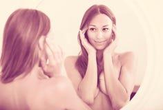 殷勤地看她自己的赤裸妇女在镜子 免版税库存图片