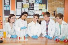 殷勤学校在实验室哄骗做一个化工实验 免版税图库摄影