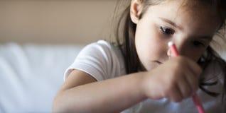 殷勤5岁儿童与毡尖的笔的女孩绘画 免版税库存图片