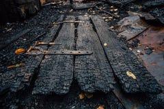 毁坏由完全地被烧的房子的火木门 库存图片