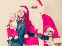 母亲、圣诞老人和两个女儿圣诞节家庭照片 库存照片