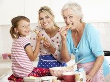 母亲、女儿和祖母烘烤在厨房里 库存图片