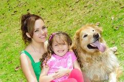 母亲、女儿和金毛猎犬尾随坐 库存图片