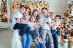 母亲、父亲和五个孩子在圣诞树附近 免版税库存图片