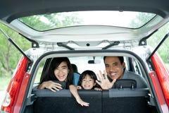 母亲、父亲和他的女儿在汽车神色里面从后窗 库存图片
