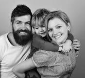 母亲、父亲和儿子有微笑的面孔的在蓝色拥抱 免版税库存图片