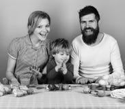 母亲、父亲和儿子有微笑的面孔的在蓝色背景 家庭准备色的鸡蛋当复活节装饰 免版税库存图片