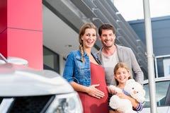 母亲、父亲和儿童买的汽车在经销权 免版税库存图片