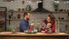 母亲、父亲和坐在桌上的婴孩在现代厨房里 爸爸和妈妈饮用的柠檬水和使用与孩子 影视素材