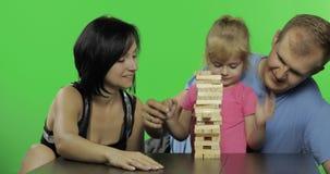 母亲、父亲和女儿播放jenga 拉扯从塔的木块 股票视频