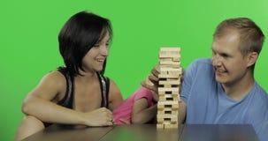 母亲、父亲和女儿播放jenga 拉扯从塔的木块 股票录像