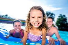 母亲、父亲和女儿游泳池的 晴朗的夏天 免版税库存照片