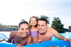 母亲、父亲和女儿游泳池的 晴朗的夏天 库存照片