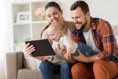 母亲、父亲和婴孩有片剂个人计算机的在家 免版税库存图片