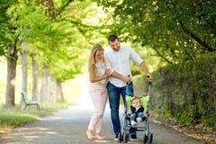 母亲、父亲和婴孩走在公园的婴儿推车的 免版税库存图片
