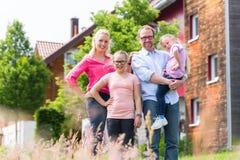 母亲、父亲和孩子在房子前面 免版税库存图片