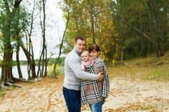母亲、父亲和小女儿是在秋天木头 免版税库存图片
