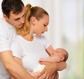 母亲、父亲和新出生的婴孩愉快的年轻家庭他们的a的 免版税库存图片