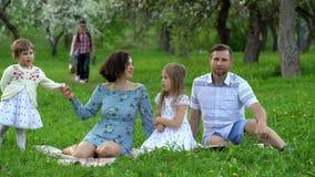母亲、父亲和逗人喜爱的女儿孩子在格子花呢披肩放松在开花的树庭院里 股票视频