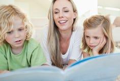母亲与她的子项的读取杂志 免版税库存图片