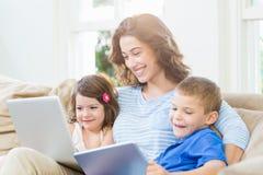 母亲与她的孩子坐沙发 免版税库存照片