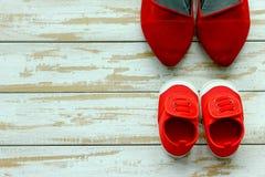 母亲两双红色鞋子或运动鞋或父亲和孩子woode的 免版税库存照片