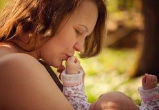 母亲亲吻她的孩子的手 概念爱母性 库存图片