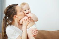 母亲亲吻她的孩子,婴孩举行他的在嘴附近的手指 库存图片