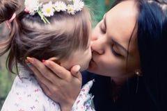 母亲亲吻她的女儿 免版税库存照片